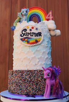 "Soaring 15"" tall into the clouds, this three-tiered My Little Pony cake, complete with rainbow sprinkles, a rainbow, marshmallow clouds, Twilight Sparkle and Rainbow Dash.  Inside: Top double tiers of Vanilla bean cake with vanilla buttercream and Bottom tier of Chocolate cake with whipped ganache buttercream, covered in rainbow sprinkles."