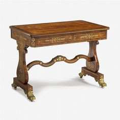Fine Regency brass inlaid rosewood sofa table   circa 1820   The rectangular top with foliate brass band and rounded corners over two frieze drawers, raised on lyre form supports united by serpentine stretcher terminating in acanthus cast gilt bronze feet, on casters.   H: 29 3/4, W: 40 3/4, D: 25 3/4 in