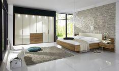 camera-da-letto-moderna-parete-mattoni-armadio-bianco-letto-legno-comodini-sospesi