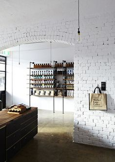 WHITE BRICK Exposed brick wall painted white, concrete floor, aged wood and industrial minimal shelves and table.