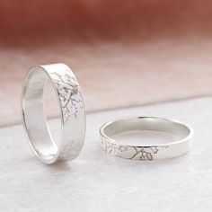 An elegant pair of wedding rings decorated with Oak leaves to symbolise strength and endurance, in Sterling SilverThe larger band is 0.5cm wide, the smaller 0.3cm wide and both are made from 0.1cm thick sterling silver sheet Choose from a single ring or a his and hers, his and his, or hers and hers matching sets. A stunning wedding ring or pair of wedding rings made especially for you, by me, in my workshop in Caerphilly, Wales. These rings will be handmade from 1mm sheet in sterling…