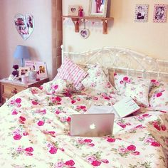 This bedroom is so girly and cute with the floral bed spread and little flag banner decorations.