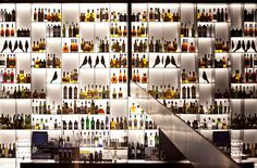 Piero Lissoni: Conservatorium Hotel, Amsterdam - wall of illuminated bottles and Eames house birds