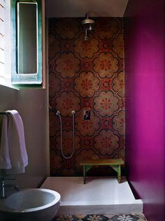 Casa Talia with a magenta accented bath/shower -- designed by architects Vivian Haddad and Marco Giunta. It is one of the Arabic houses in the Medina-inspired hotel located in Modica, Italy.