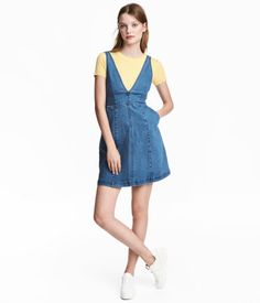 Denim blue. Short, sleeveless dress in washed stretch denim. Low-cut V-neck at front and back, seam at waist, and side pockets.