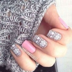 Cute and adorable looking winter nail art.  Pixel inspired patterns and snowflakes are painted in white polish on top of periwinkle and baby pink backgrounds.