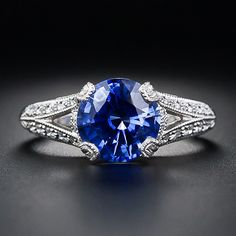 A scintillating, electric-blue, faceted round sapphire, weighing 2.75 carats, is tastefully presented in this newly made platinum and diamond mounting, meticulously crafted in timeless vintage style. Tiny, sparkling, full-cut diamonds surround the sapphire and continue down split 'V' shape shoulders in finely milgrained settings. This superb and stunning sapphire ring is finished with a lovely neo-classically inspired openwork gallery and leafy hand-engraving along the ring shank. A gorgeous…