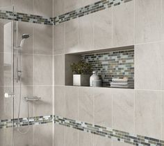 Photo features Daltile Avondale wall tile in Castle Rock with Glass Horizons random mosaic tile in Arctic Blend used as trim and in the alcove.