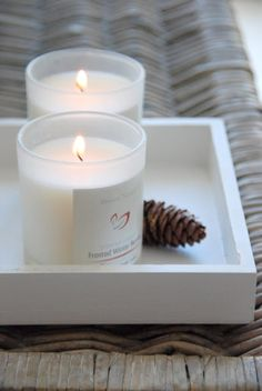simple white tray with white candles on a wicker coffee table