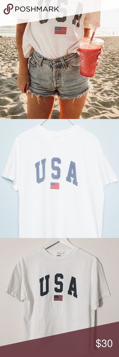 NWT Brandy Melville Aleena USA Tee - new with tags still attached. so sad to sell this but i'm not going to wear it :( this will come with a small surprise, so price is firm on this one; no exceptions! soft cotton tee in white with USA graphic printed in blue with USA flag embroidery.  - ONE SIZE Brandy Melville Tops Tees - Short Sleeve