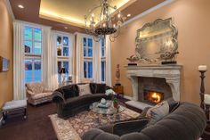 A fabulous living room with regal decor like this antique chandelier, large mirror, and warm marble fireplace. Mercer Island, WA Coldwell Banker BAIN $5,695,000