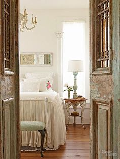 Oh, I love those antique doors to this beautiful white bedroom!