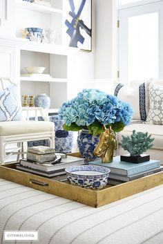 Spring coffee table styling with blue faux hydrangeas, design books, coral and beautiful objects. #springdecorating #coffeetablestyling #coffeetableideas #fauxhydrangeas #homedecoraccessories