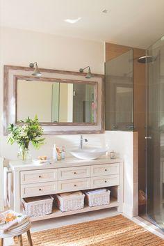 Baño con cómoda reconvertida en mueble bajolavabo y cabina de ducha