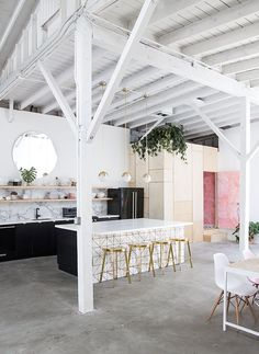 Open plan kitchen and living space. Love the white and gold tiles on the island unit that serves as a seating area with gold bar stools. The black kitchen units and marble splash backs give a glamorous feel. The open shelving feels more relaxed.