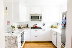 """I think we need to coin a new term. I'm calling it """"livably minimalist,"""" and using it to describe those clean, mostly-white spaces that appeal to our spartan sensibilities, but which still showcase some of the comforts of home. In other words, like a seriously cool futurist catalog kitchen, but one that looks like somebody actually lives there."""