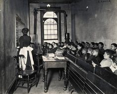 Teacher Instructing Schoolboys in Small Classroom. 1902, New York City — A classroom full of children in the condemned Essex Market School. A teacher demonstrates on the blackboard, as students watch attentively from crowded pews. Note the open gas jets near the ceiling used for lighting. — Photo by Jacob Riis, Image © Bettmann/Corbis