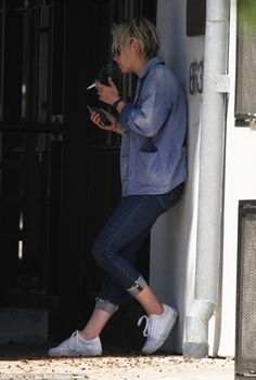 Staying in the loop: Kristen glanced down at her phone in her free hand...