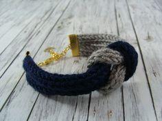 Blau trift grau: so schlicht und doch so schön. Die beiden gestrickten Bänder sind verknotet und werden durch einen maritimen Anker gekrönt.    Das Armband ist ca. 16 cm lang und hat noch ein...
