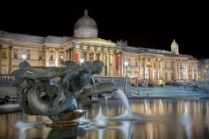 A night shot of a fountain in Trafalgar Square with the National Gallery in the background.<br /> <br /> David Henderson Photography Fine Art Print