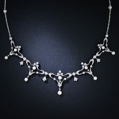 An exquisite turn-of-the-century necklace exhibiting consummate Edwardian style with a dash of Art Nouveau artistry. This ultra-charming necklace, lovingly hand crafted in platinum over gold, is comprised of five gently graduated sections designed with delicately stylized whiplash motifs, small sparkling diamonds and lustrous natural pearls. The original platinum neck chain is punctuated with bezel-set diamonds. A truly wonderful and ravishing antique necklace - circa 1900.
