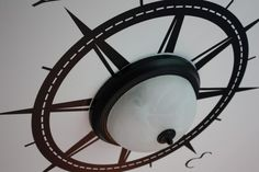 I like the idea of putting the compass around the light/fan - wonder if this is possible in his room?
