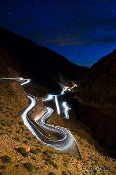 Cars leave light trails as they travel on the winding roads of the Dades Gorge Morocco at night. The Road, Beautiful Roads, Beautiful Places, Roads And Streets, Cap Vert, Dangerous Roads, Light Trails, Winding Road, To Infinity And Beyond