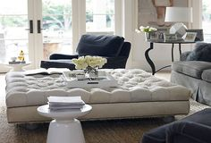 An oversized tufted ottoman with plush velvet sofas with modern lines for a New Romantic living space
