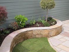 Mixed planting in a raised bed constructed with Quartz stone and sandstone wall capping.
