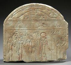 SOMMET DE STÈLE cintrée sculptée d'une femme vêtue d'une longue tunique frangée en adoration face au dieu Rê-Horakhty hiéracocéphale, suivi d'Osiris momiforme protégé par Isis et Nephtys; des colonnes hiéroglyphiques identifient les divinités. La scène est surmontée du signe du ciel et du disque ailé de Béhédet nommé deux fois. Calcaire et traces de polychromie. Égypte, Basse Époque.