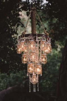 This is so cool! Vintage wedding decor with mason jar wagon wheel chandelier