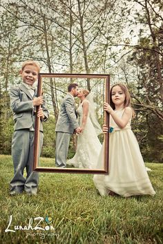"""A Love-ly work of art! Ring-bearer and flower girl hold up a frame to """"frame"""" the bride and groom. @Tommy ☺ Watson How cute would this be!"""