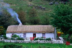 A farm house with smoke blowing from the chimney, Glengesh Valley, Ardara, County Donegal, Ireland.