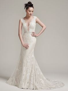 Wyatt by #SotteroandMidgley Sophisticated and effortlessly glamorous, this modern lace sheath wedding dress flaunts a sexy, plunging illusion neckline, beaded belt, and lace cap-sleeves. Complete with illusion back with ruched details. Finished with pearl buttons over zipper closure.