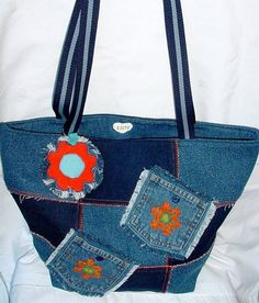 An eye catching denim tote bag made from two tones of blue denim fabric, patch worked together with bright orange thread. Crochet flowers and a