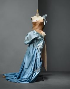 House of Dior (French, founded 1947), John Galliano (British, born Gibraltar, 1960). Ensemble, autumn/winter 2005–6, Haute Couture. Machine–sewn nude silk satin, hand–stitched white polyester batting, hand–draped and –basted nude silk net and hand–piece–dyed blue silk taffeta, hand–embroidered with clear glass beads, opalescent rhinestones, blue and ivory chenille,and silver metal cord and strips.Photo © Nicholas Alan Cope. #ManusxMachina #CostumeInstitute