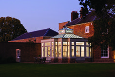 An illuminated orangery at dusk