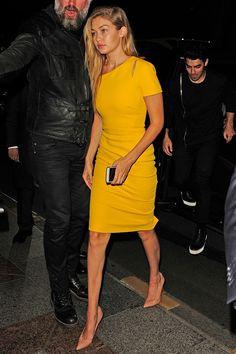 Gigi Hadid - vestido entubado de color amarillo con cut outs en los hombros de Victoria Beckham y salones Completa de charol nude de Christian Louboutin.