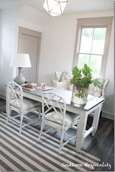 greige trim with white walls, settee, large work table, light fixture