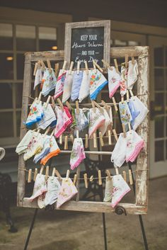 Handkerchief board display for your wedding guests. Photo by @billiejojeremy. #charlestonwedding #alhambrahall #handkerchiefdisplay #weddingdetails #southernweddings #outdoorweddings #clothespins #pictureframe #chalkboard