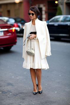 Oversized white blazer, white shirt, white accordion pleated midi skirt, and black heels