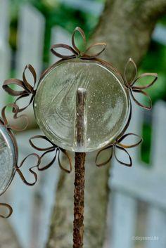 Seit vier Jahren gibt es Glasvasen-Beetstecker in unserem Garten. 70er-Jahre Mono-Block-Glasvase plus Moniereisen = Beetstecker. Meine September Stahlbandidee ist ein einseitig offener Motivkranz, den ich um die Vase herum legte. In ein ca. 1 Meter langes Stück Stahlband werden aus der Mitte heraus mehrere Dreiblatt-Verzierungen in gleichmäßigen Abständen gearbeitet, zu …