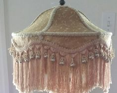 This is an enchanting shade made of Venice Embroidered Lace. It has a beige base fabric with an sheer embroidered overlay of green, brown and gold. The gimp/trim is gold and green. And I have added a beaded trim to compliment the 5 gold fringe.  Measurements: 11 Tall which includes the 5 fringe. 17 x 10 1/2