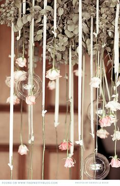 Roses hung upside down at the ends of ribbon streamers. Would be a great use for custom imprinted continuous ribbon rolls! You could have names, quotes, or whatever printed on the ribbon. Could hang from wreath for chandelier (with pearls?)