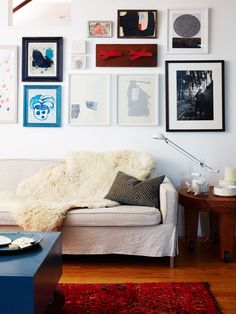 A mix and match gallery wall hangs above a linen-covered sofa and sheepskin throw in a rustic Maine home.