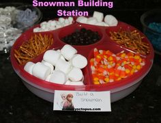 Snowman Building Station – includes big and small marshmallows, pretzel sticks for arms, chocolate chips for eyes or buttons, and candy corn nose.