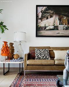 Sala tem sofá de couro, almofadas e tapete étnico e muitas peças de artesanato brasileiro.