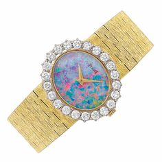 This has to be the prettiest face I have ever seen on a watch... Lady's Gold Piaget watch, Opal Doublet and Diamond Wristwatch, 18 kt., mechanical, centering an oval opal doublet dial, surrounded by 22 round diamonds approximately 2.20 cts., completed by a textured gold bracelet, (sold for 5313.00)
