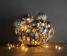 Create a glowing holiday centerpiece by filling ornaments and glistening lights in a modern bowl.