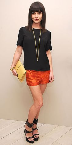 summertime style in a black top, orange shorts, strappy sandals and a colorful clutch